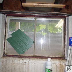 An old, rusted basement window with a steel frame in 7].